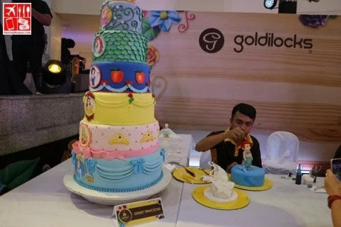 A Goldilocks cake decorator working on his masterpiece