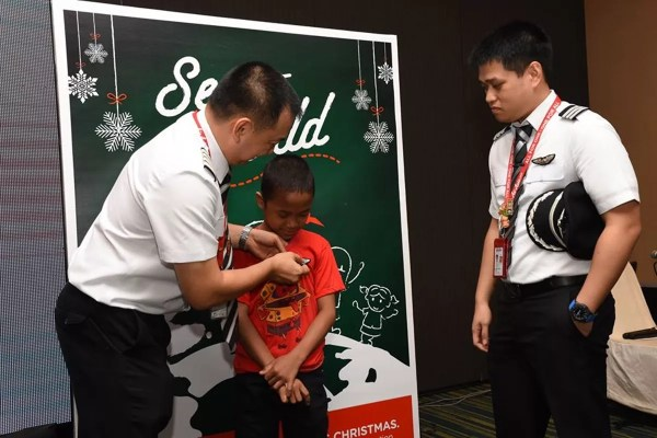 Capt. Darren Acorda and First Officer Andre Abacan awards an AirAsia Pilot's badge to a World Vision sponsored child who dreams of becoming a pilot