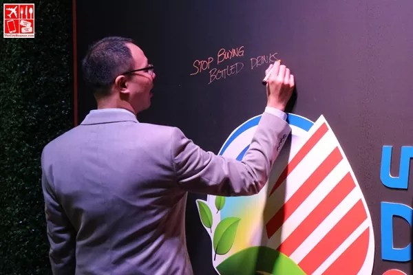 Kenneth Pundanera writes his pledge on the Unioil Doing Our Part commitment wall