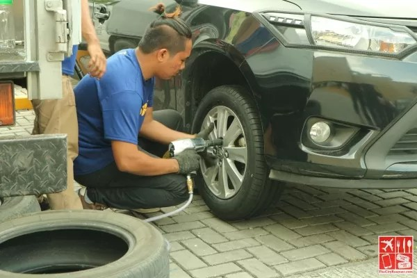 A Goodyear staff works on replacing the tire of a car