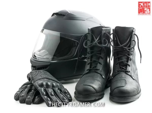Motorcycle helmet, gloves and boots isolated on white background.