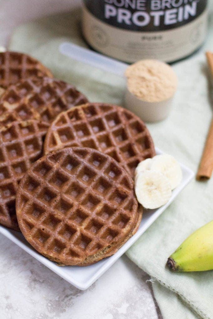 Fluffy Healthy Blender Banana Bread Protein Waffles on a long square plate with a scoop of protein powder, banana and cinnamon sticks on a light green towel.