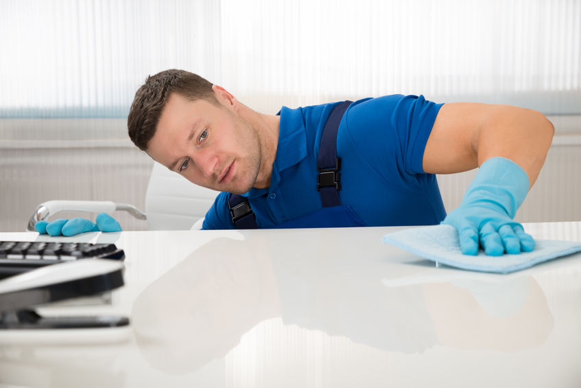 Janitor Cleaning Desk With Sponge At Office