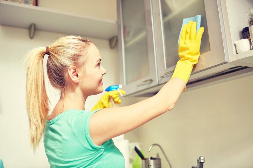 happy woman cleaning cabinet at home kitchen