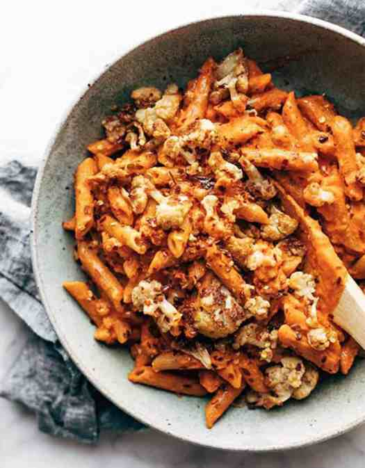Red pepper penne with cauliflower on a grey plate with a wooden spoon - Pinch of Yum