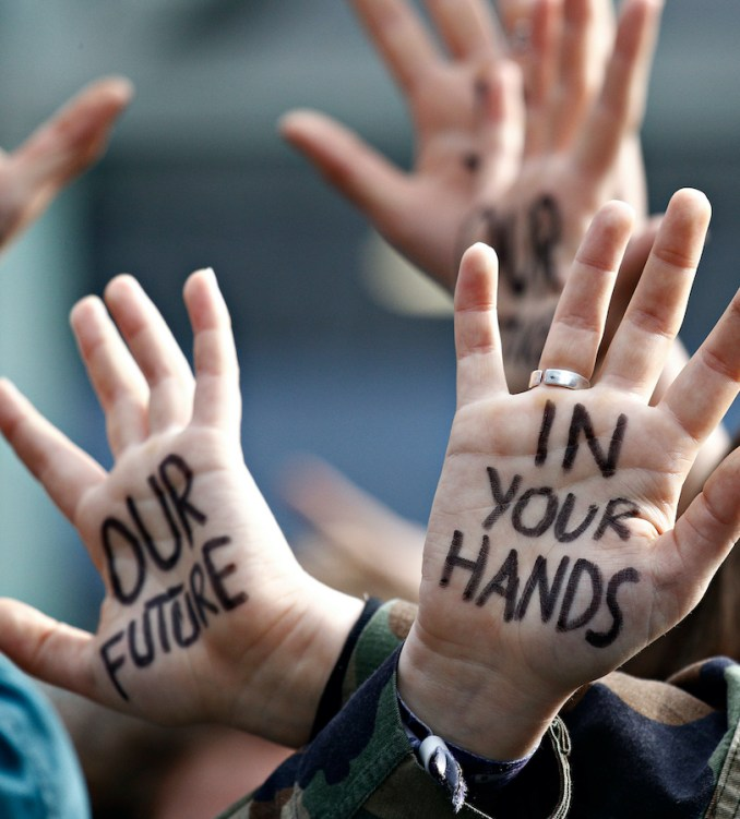 Image of hands with writing on them from climate protest