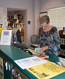 Coaster Photo - Neptune City Head Librarian Patty Scott sorts through books at the libary which is celebrating its 90th year.