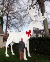 Coaster Photo - Professional woodworker Dave Gallina stands by his 15-foot-high wooden reindeer on his front lawn in the West Allenhurst section of Ocean Township.