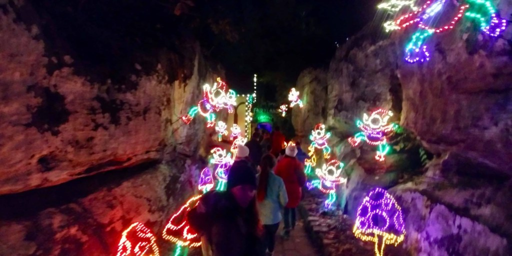 Walking through caves decorated with Christmas lights