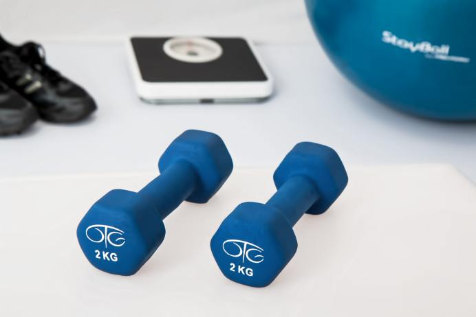 Dumbbels on floor next to shoes, scale, and ball