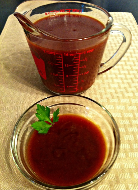 Measuring cup and bowl of homemade BBQ sauce