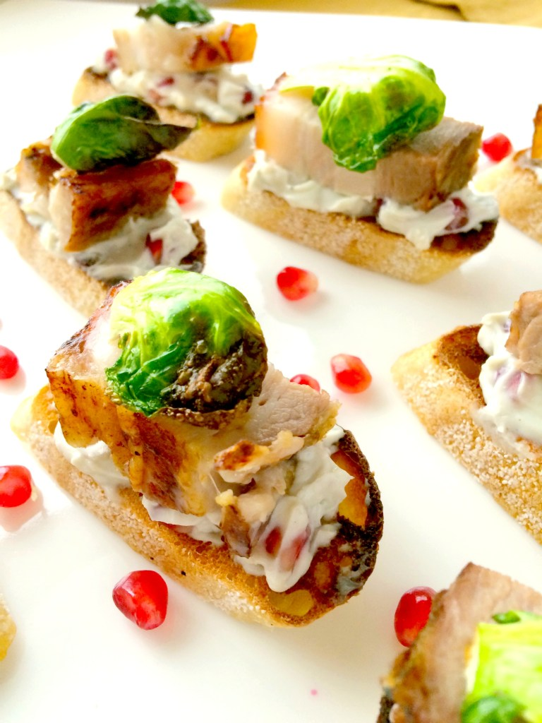 Pomegranate Pork Belly Crostini ~ Baguette layered with a bleu cheese pomegranate spread topped with a succulent slice of pork belly and roasted Brussels sprout chip ~ The Complete Savorist
