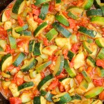 Zucchini and tomatoes in a cast iron skillet.