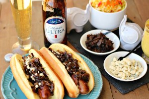 Two brats with caramelized onions and blue cheese with a beer.