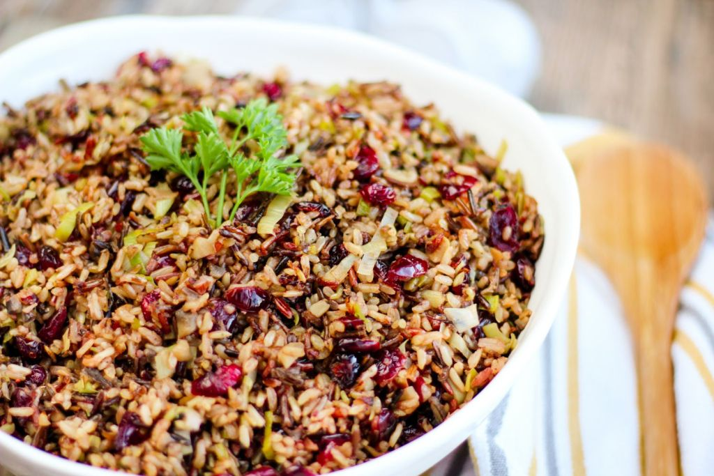 Bowl of wild rice with mushrooms, cranberries, leeks, herbs, and seasonings.