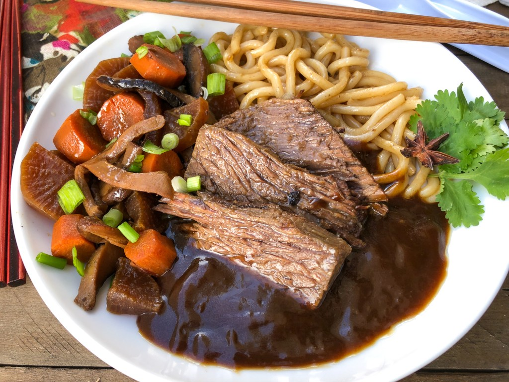 Individual portion of Japanese pot roast with daikon, carrots, mushrooms, udon noodles, and gravy.