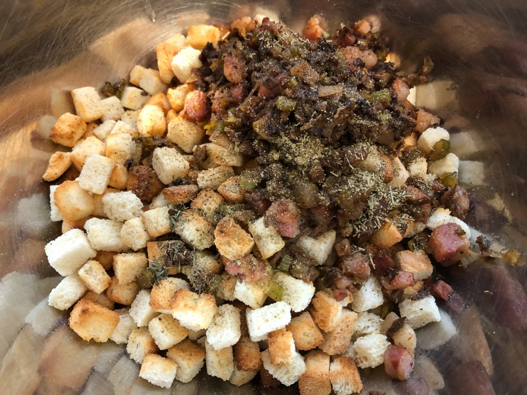 Bread, seasonings, sautéed vegetables and pancetta have been added to a large stainless steel bowl.