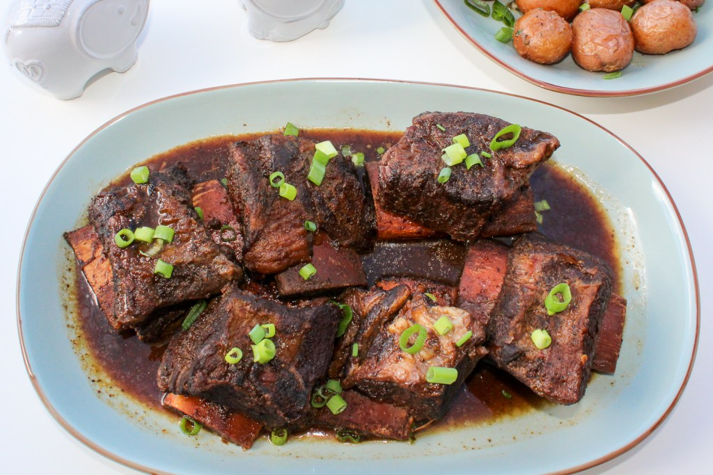 Top-down view of short ribs in a orange honey hoisin sauce garnished with scallions.