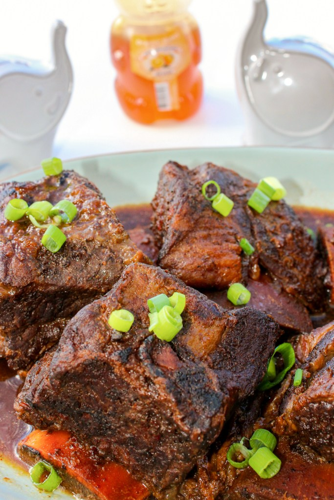 Orange Honey Hoisin Short Ribs served on a blue platter.