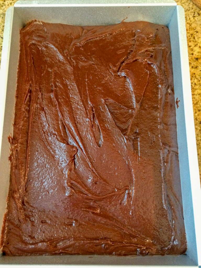 Brownie batter poured and smoothed into a prepared baking pan.