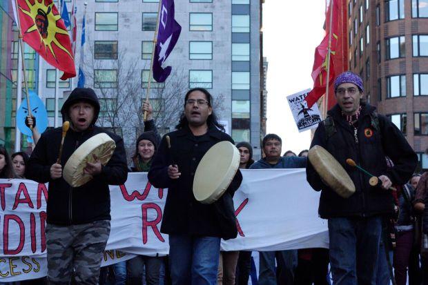 Jesse Achneepineskum marches towards the banks on Nov. 7. Photo by Savanna Craig,