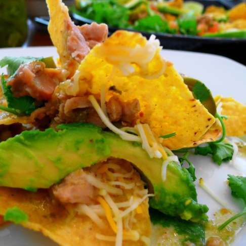 On the plate nachos with chile verde sauce