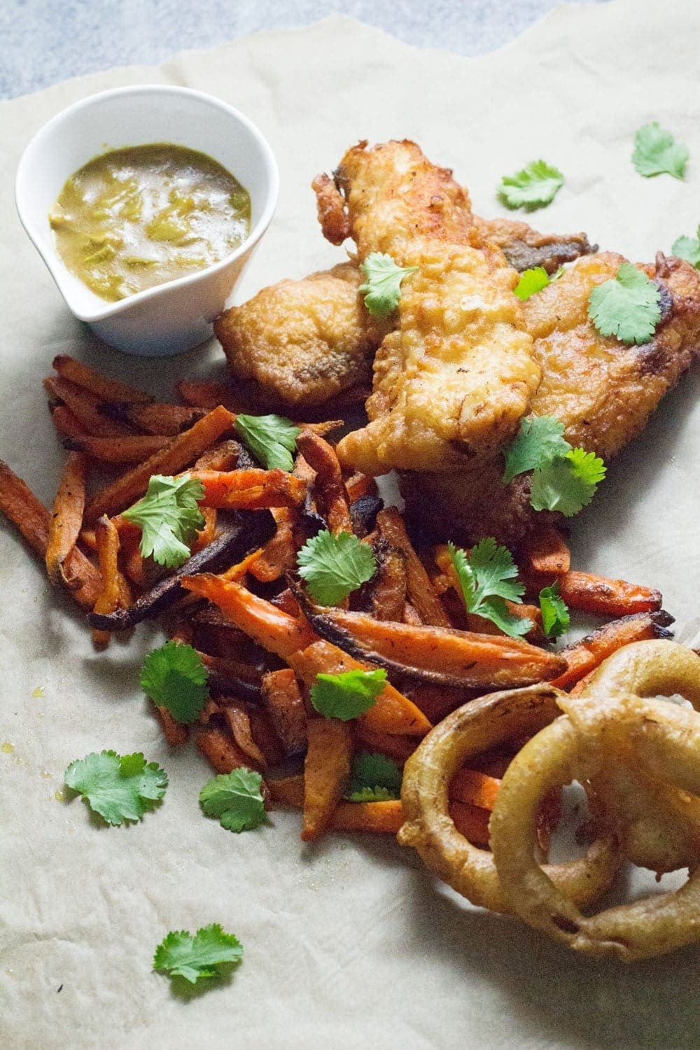 This Caribbean style fish and chips is made up of rum battered fish, sweet potato fries, jerk onion rings and an incredible coconut curry sauce!