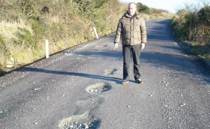 Councillor Jim Daly inspects some of the potholes.