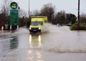 An ambulance makes it's way through the flooded road at Ballinscarthy, West Cork yesterday. Photo: Billy macGill