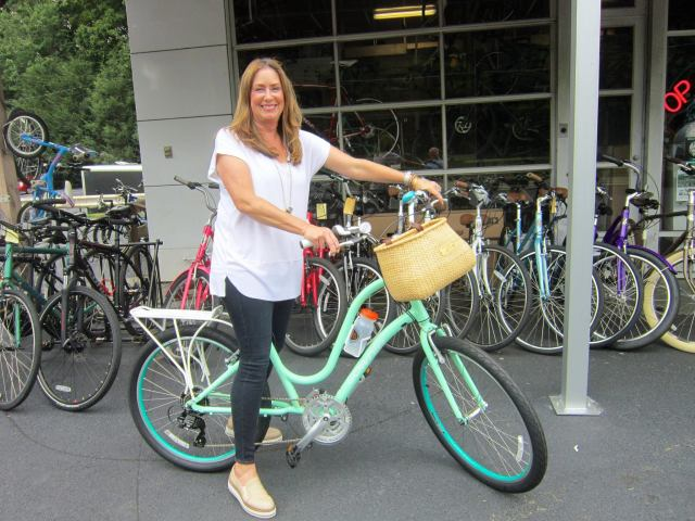 A happy woman with her bike