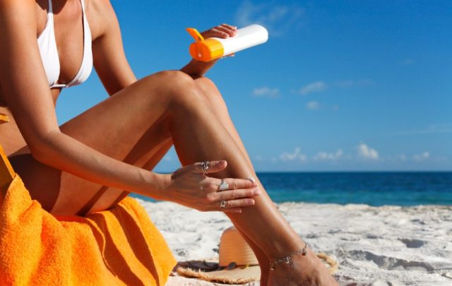 Woman applying sunblock on her legs