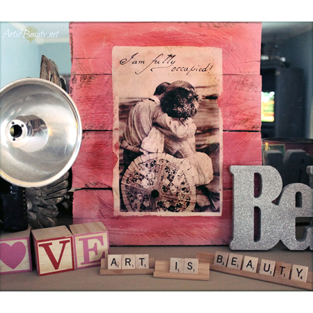 The Graphics Fairy made this pallet wall art with a vintage photograph pasted and vibrant red wine stain