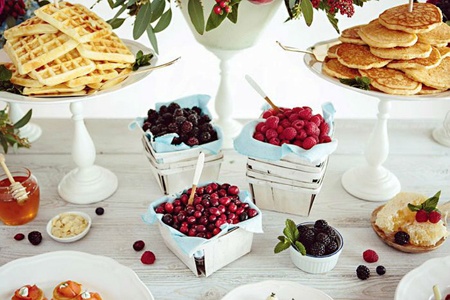 A breakfast bar with pancakes, waffles, and delicious toppings is a creative way to add great food to your party
