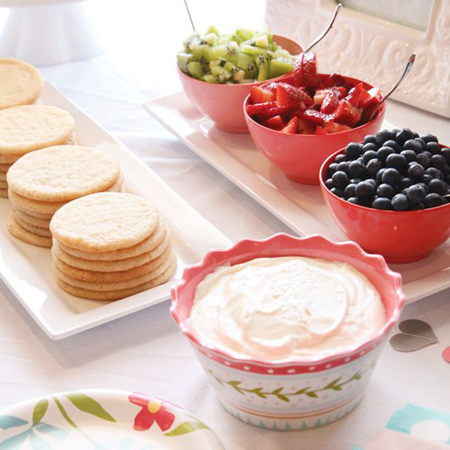 This cookie bar is a special kind of creative graduation party food idea. Sugar cookies, vanilla frosting, and a variety of fruit to top your sweet treat