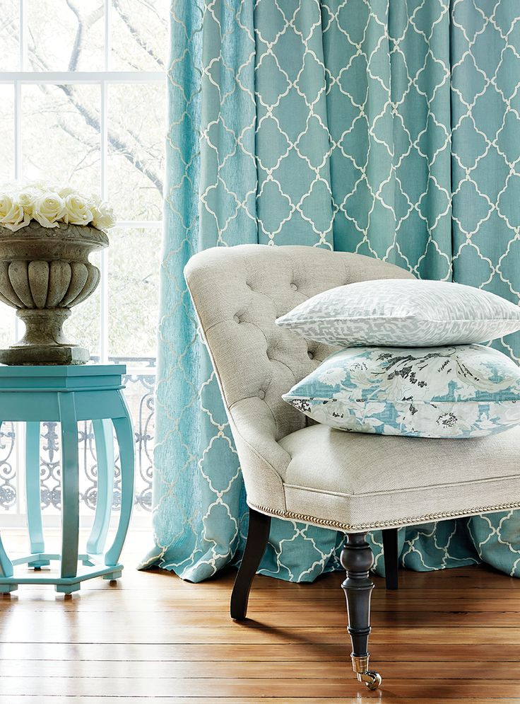 In this living room, we see aqua in the side table, throw pillows and curtains