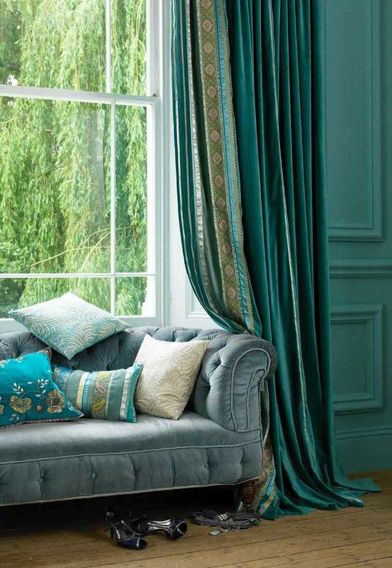 Various shades of blue - from bight aqua throw pillows to deep navy curtains makes a bold statement in this room