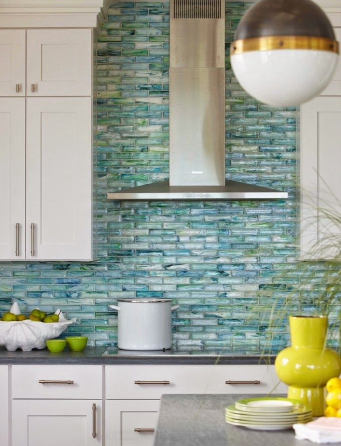 The stunning aqua backsplash in this kitchen adds so much color against the white cabinets