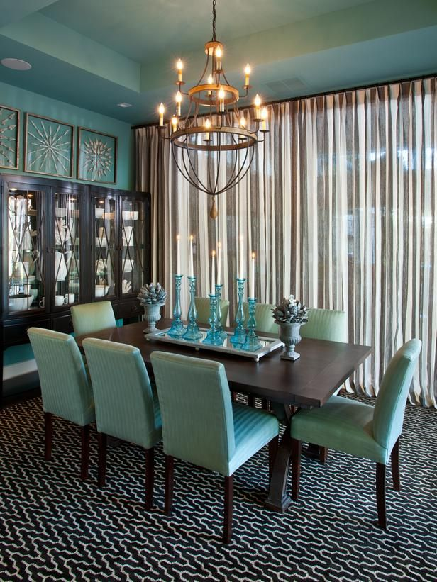 This dining room uses aqua on the walls and dining room chairs while other colors like gold and black balance it out