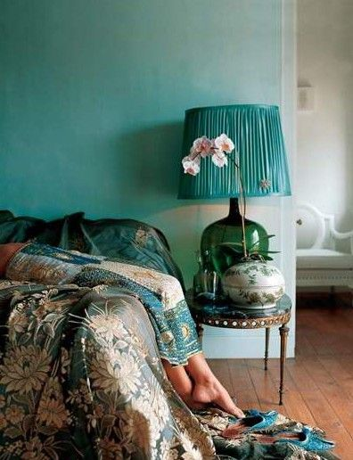 The aqua colored wall pairs perfectly with the dark silk floral bedding