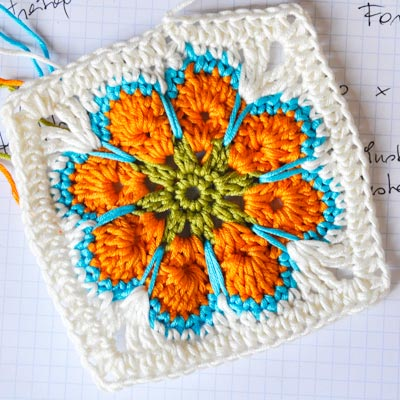 This orange crocheted flower on this granny square looks great with the blue yarn outline.