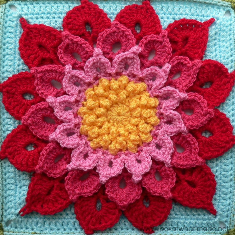 This large crocheted flower with a yellow center and pink petals is so cute.