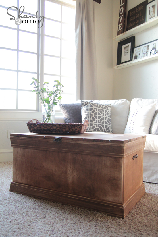 This rustic wooden chest is distressed and adds a farmhouse element to the modern living room.
