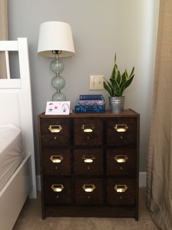 This wood apothecary tables with gold accents works great as a nightstand.