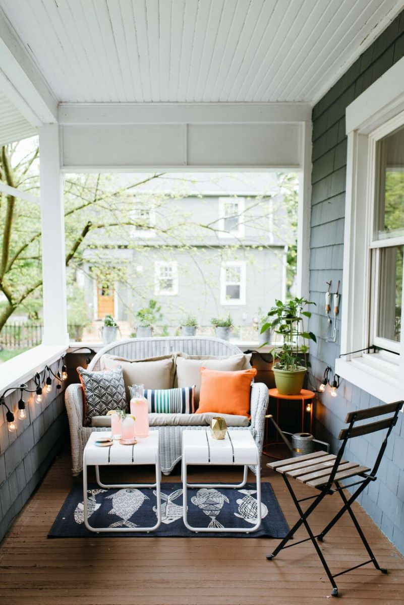 Simple furniture like this wicker lounger and metal tables give this small patio space an upgrade
