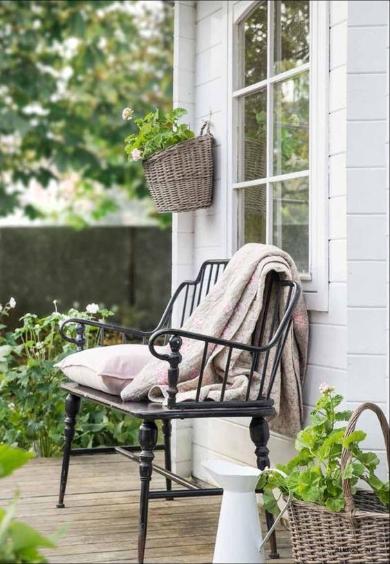 This simple wrought iron chair with a pillow and a throw spruces up this small porch area