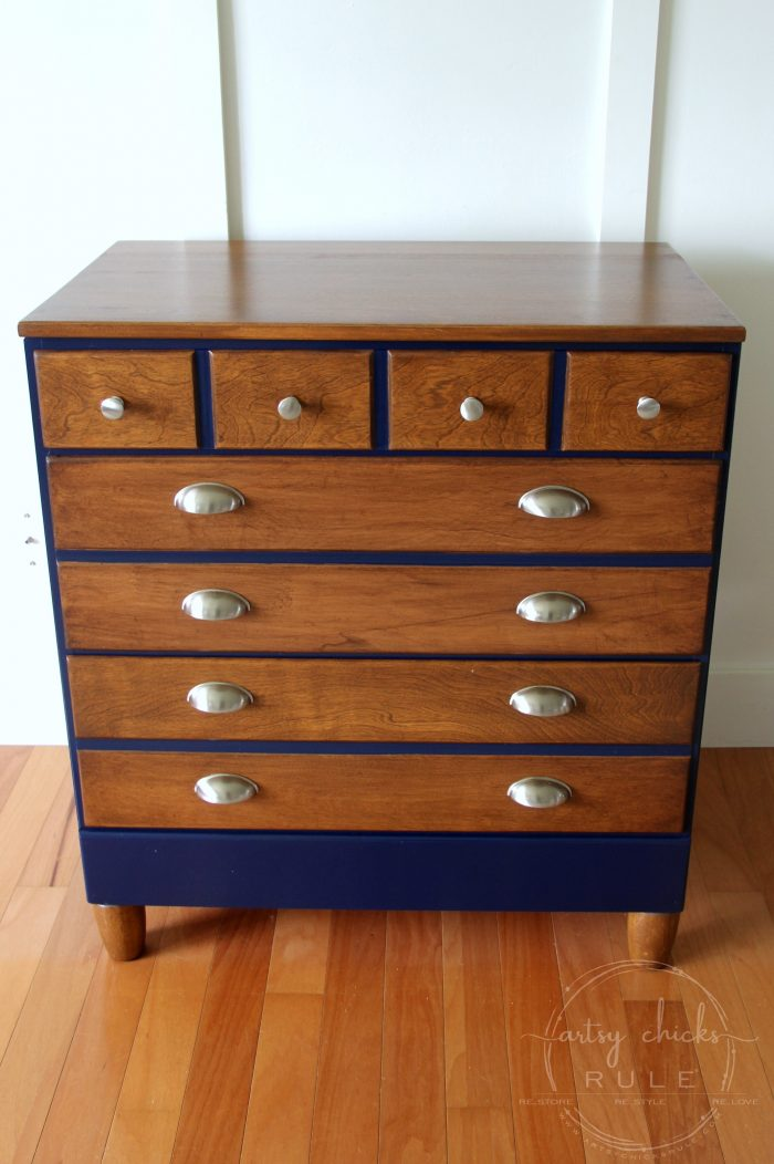 This wooden dresser with a blue accent color and silver hardware is modern.
