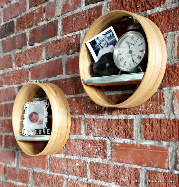 These floating wooden circular shelves with a silver accent compliment the brick wall.