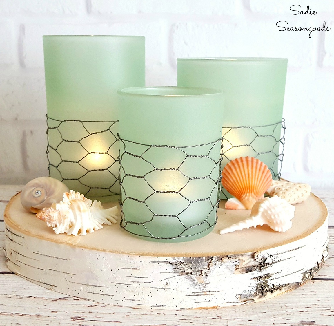 These sea glass candles resting on a piece of wood are coastal and farmhouse chic.