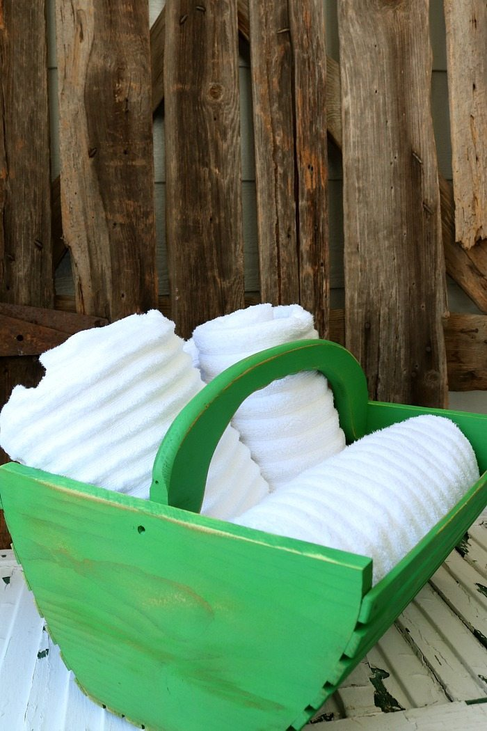 This updated wooden basket painted green is great for storing towels.