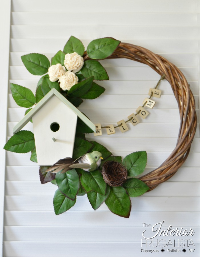 This spring wreath has a cute birdhouse and welcoming banner that's perfect for spring decor